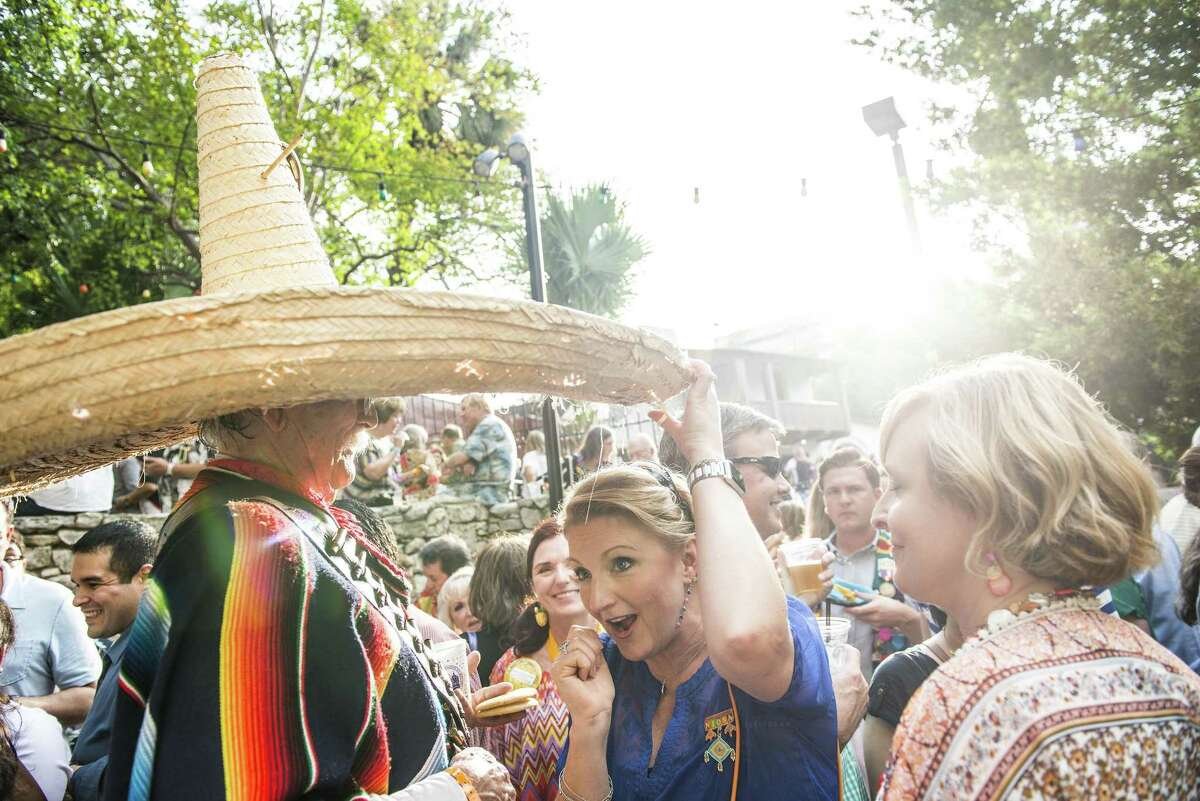 """A woman tries to hide under Lloyd Jary or """"Poncho Villita's"""" 30+ year old sombrero as he greets friends at NIOSA during Fiesta week in San Antonio, Texas in La Villita on Tuesday, April 19, 2016."""