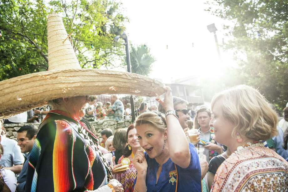 "A woman tries to hide under Lloyd Jary or ""Poncho Villita's"" 30+ year old sombrero as he greets friends at NIOSA during Fiesta week in San Antonio, Texas in La Villita on Tuesday, April 19, 2016. Photo: Matthew Busch, Stringer / For San Antonio Express-News / © Matthew Busch"