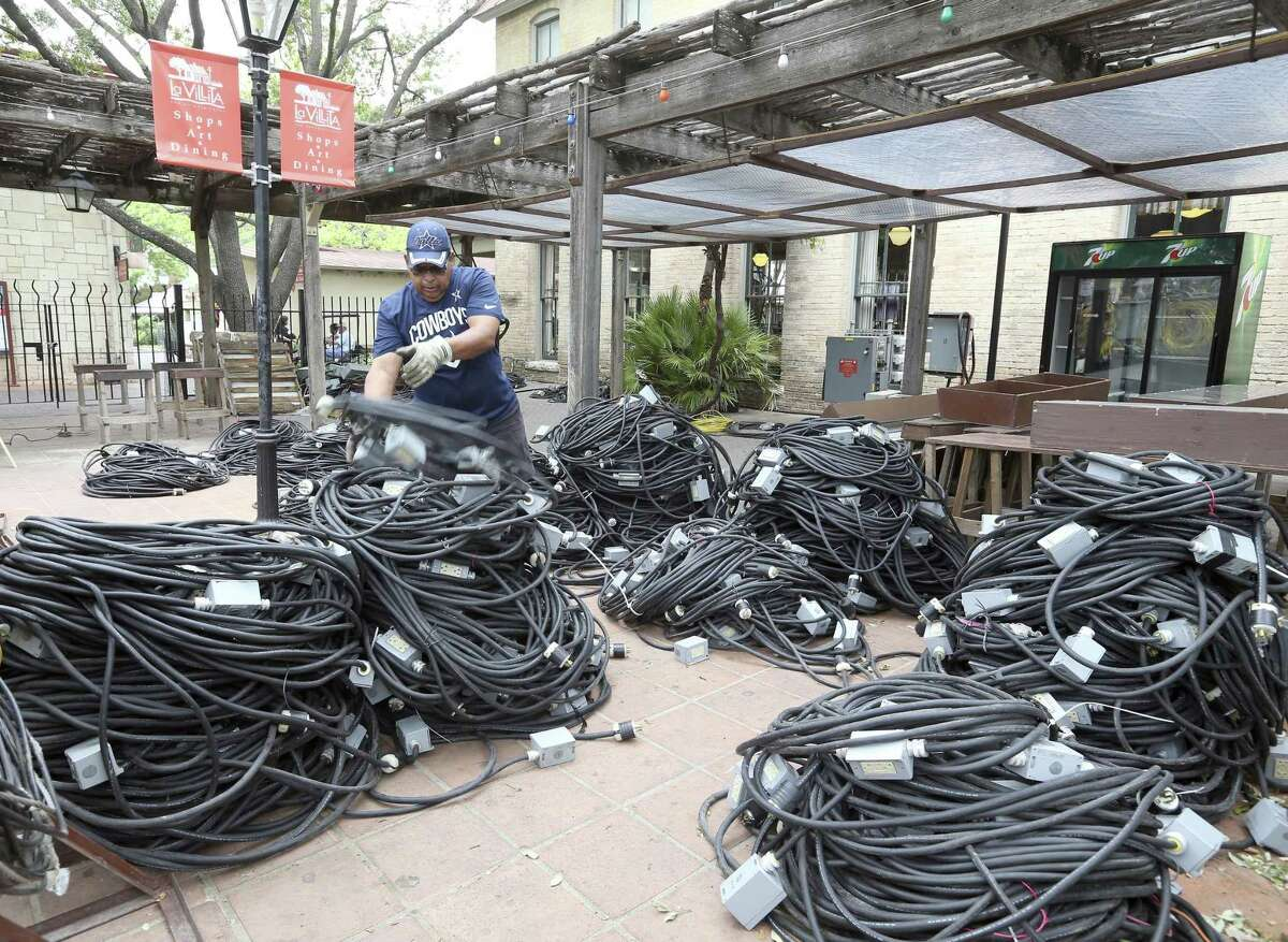 Hank Cortez deals with wires Wednesday, April 18, 2018 of some of the many temporary electrical circuits being installed on the La Villita grounds for A Night in Old San Antonio which runs April 24-27.
