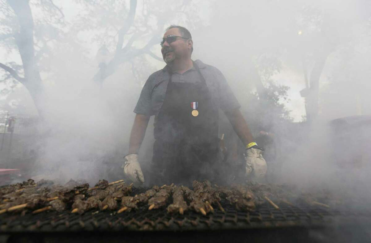 Armando Rodriguez is swallowed in smoke as anticuchos cook on a hot grill at the 2015 Night In Old San Antonio at La Villita on Tuesday, Apr. 21, 2015. The smell of food and the sounds of music filled the sky as patrons make the slow crawl in search of anticuchos or chicken on a stick. Some adorned colorful headwear but many just gathered for the annual fiesta event which benefits the San Antonio Conservation Society. The skewers of beef are a big seller every year at NIOSA. (Kin Man Hui/San Antonio Express-News)