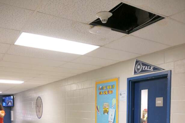 Exposed ceiling panel, water marked panel, a trash can to capture leaking water and a wet floor sign are a common sign at Cigarroa High School every day it rains.