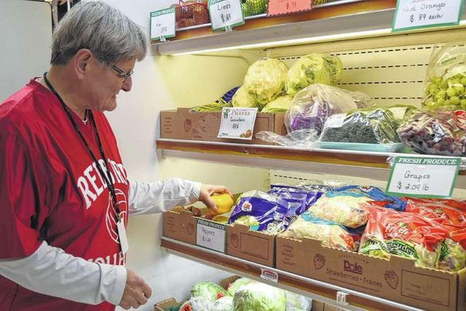 Stephanie Hobrock, manager of McCausland's Food Market, examines some of the store's fresh produce on March 14. Photo:       Samantha McDaniel-Ogletree | Journal-Courier