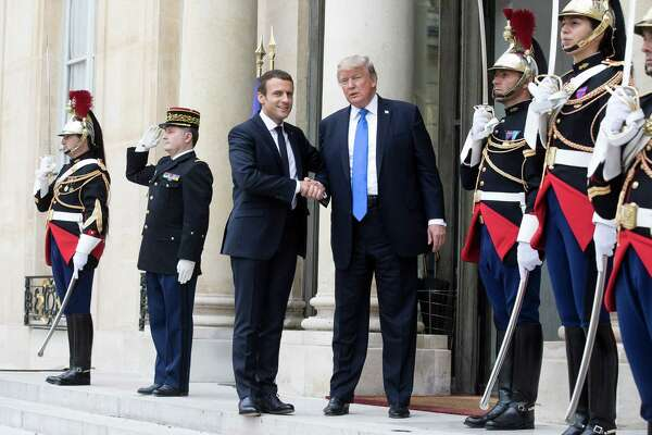 French President Emmanuel Macron (left) and President Donald Trump shake hands at the Elysee Palace in Paris on July 13, 2017.