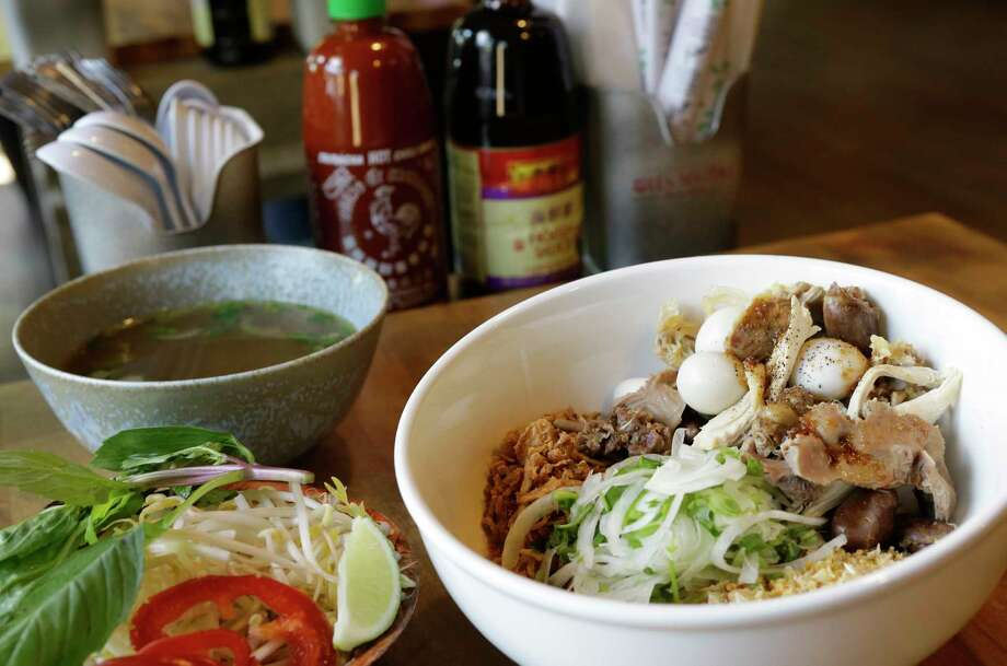 Dry free-range chicken pho with broth on the side is  at Les Noo'dle, 1717 Montrose. The owners of the former Les Ba'get have changed the focus of their Montrose restaurant to specializing in pho. Photo: Melissa Phillip, Houston Chronicle / © 2018 Houston Chronicle