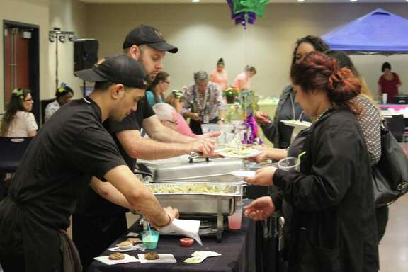 Michael Sosef (left) and David LeGrande (second from left) of Italianos provide Italian dishes to visitors at the April 18 Taste of Cleveland event.