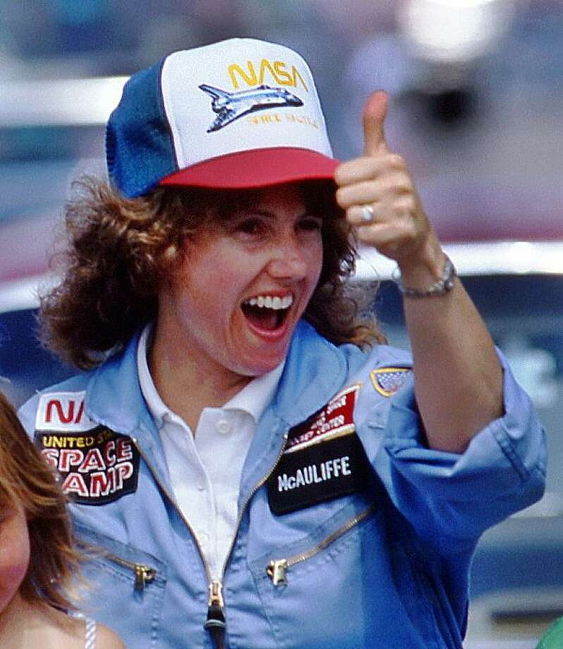 In this 1985 photo, high school teacher Christa McAuliffe gives a thumbs-up during a parade down Main Street in Concord, N.H. McAuliffe was one of seven crew members killed in the Space Shuttle Challenger explosion on Jan. 28, 1986. (AP Photo/Jim Cole) Photo: Jim Cole / Associated Press / AP