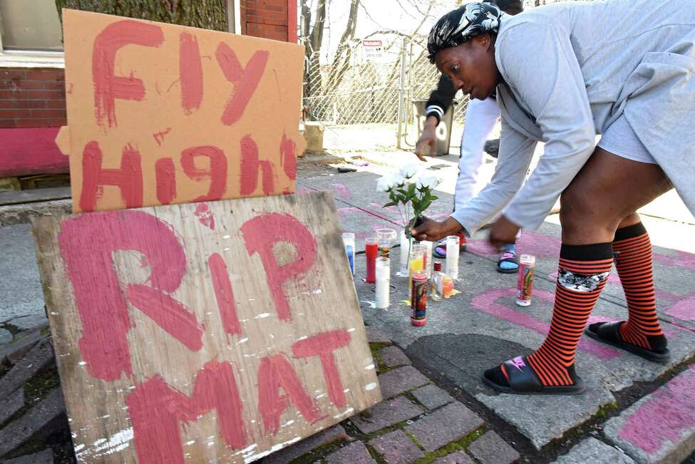 Patricia McMillian of Albany places flowers on a memorial for her friend on Clinton St. near Second Ave. on Monday, April 23, 2018 in Albany, N.Y. She arrived with Keessence Coles of Albany to pay respect and light a candle for their friend who was shot multiple times in this location on Sunday afternoon.Their friend was identified by police as 38-year-old Damien L. Sanders, who was shot multiple times in this location on Sunday afternoon. (Lori Van Buren/Times Union)