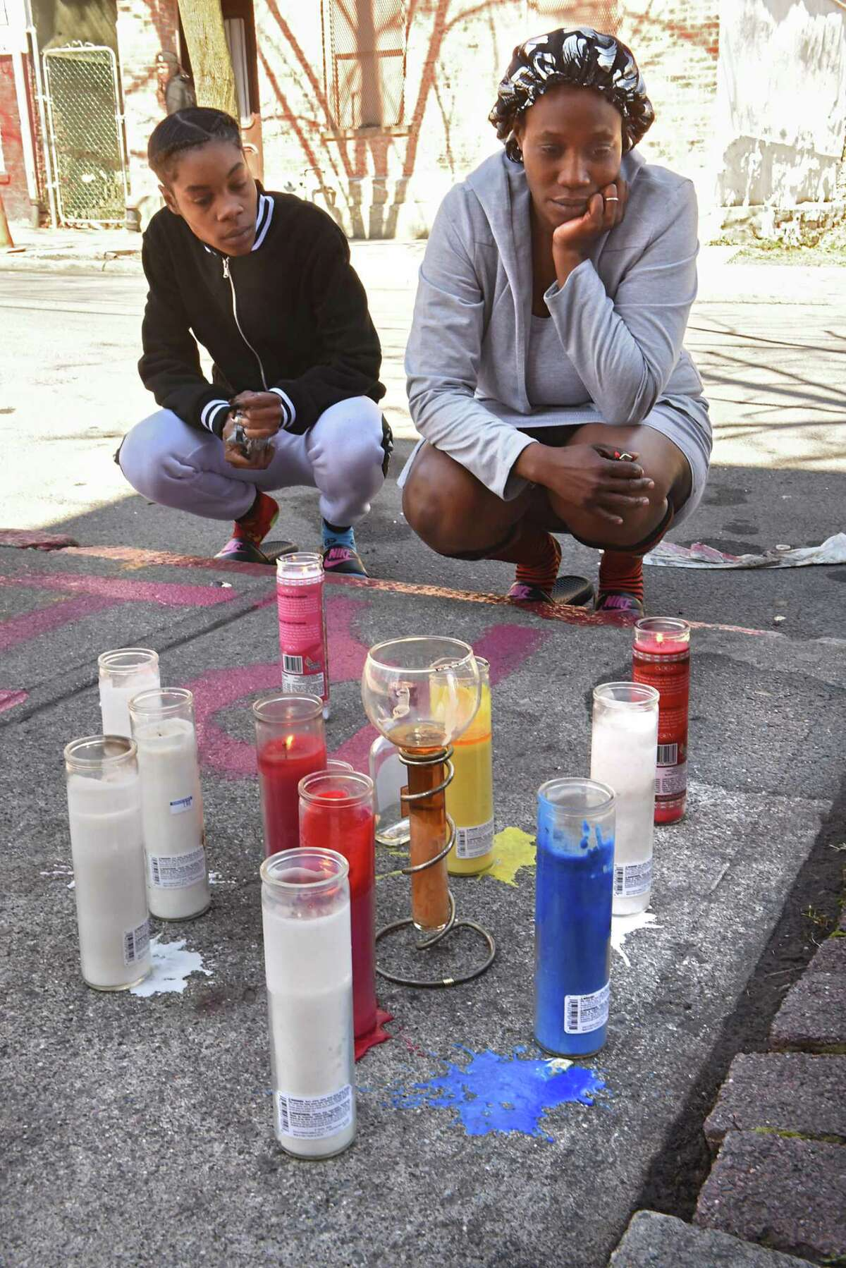Keessence Coles, left, and Patricia McMillian, both of Albany, take a moment of silence after bringing flowers and lighting a candle they also brought for their friend's memorial on Clinton St. near Second Ave. on Monday, April 23, 2018 in Albany, N.Y.Their friend was identified by police as 38-year-old Damien L. Sanders, who was shot multiple times in this location on Sunday afternoon. (Lori Van Buren/Times Union)