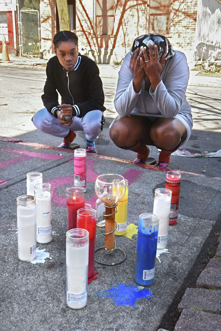 Keessence Coles, left, and Patricia McMillian, both of Albany, take a moment of silence after bringing flowers and lighting a candle they also brought for their friend's memorial on Clinton St. near Second Ave. on Monday, April 23, 2018 in Albany, N.Y. Their friend was identified by police as 38-year-old Damien L. Sanders, who was shot multiple times in this location on Sunday afternoon. (Lori Van Buren/Times Union)