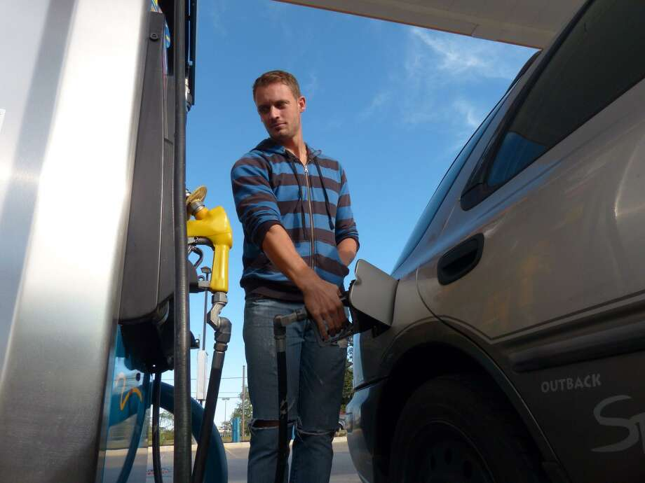 UTSA student Michael Gomm fills up at the Valero Station at 5602 UTSA Blvd on Friday, Oct. 31, 2014. Photo: Billy Calzada /San Antonio Express-News / San Antonio Express-News