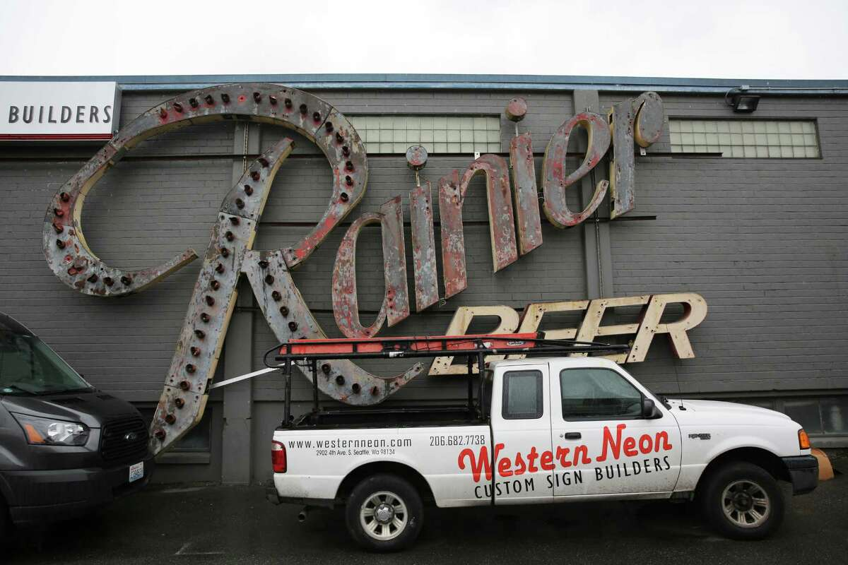 """An original Rainier Beer sign hangs on an exterior wall of the Western Neon shop in Sodo. The Western Neon team fabricated the new Rainier """"R"""" that was placed atop the old Rainier Brewery in Georgetown in 2013."""