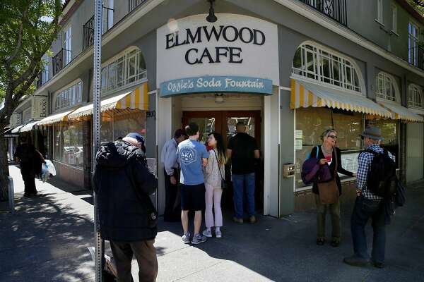 People gather at the front door of the Elmwood Cafe on College Ave. to read the sign about the sudden closure of the Cafe as seen on Fri. April 20, 2018, in Berkeley, Calif.