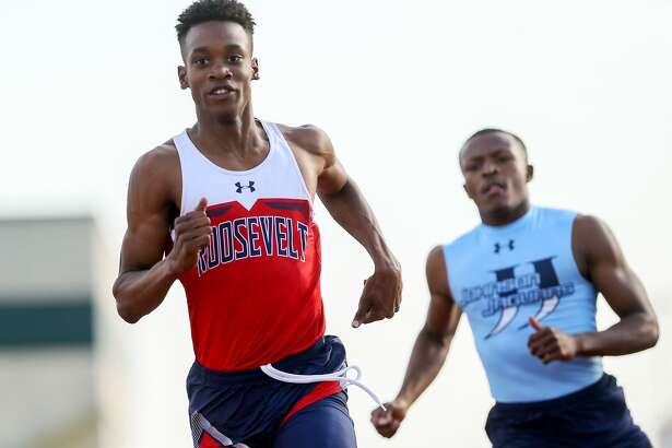 Roosevelt's Nazzio Jack John (left) runs through the finish linein the boys 100-meter dash with Johnson's Jabari Aiken during the District 25/26-6A area meet at Gustafson Stadium on Thursday, April 19, 2018.  Jack John won the event with a time of 10.90 seconds.  He later won the 200-meter run.  MARVIN PFEIFFER/mpfeiffer@express-news.net