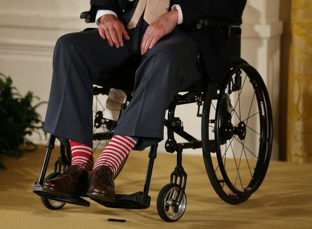Bush wears red stripped socks as he sits in a wheelchair during an event in the East Room at the White House, July 15, 2013, in Washington, D.C. Bush joined President Barack Obama in hosting the event to honor the 5,000th Daily Point of Light Award winner. Photo: Mark Wilson/Getty Images