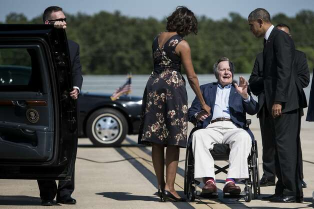 Bush greets President Barack Obama and first lady Michelle Obama at Bush Intercontinental Airport on April 9, 2014, in Houston. Obama, who attended a memorial service at Fort Hood, was in Houston to attend two fundraisers for the Democratic National Committee, the Democratic Congressional Campaign Committee and the Democratic Senatorial Campaign Committee. Photo: BRENDAN SMIALOWSKI/AFP/Getty Images