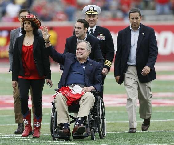 Bush waves to the crowd as University of Houston President Renu Khator, left, walks beside him at TEDECU Stadium on Nov. 27, 2015, in Houston. Photo: Bob Levey/Getty Images