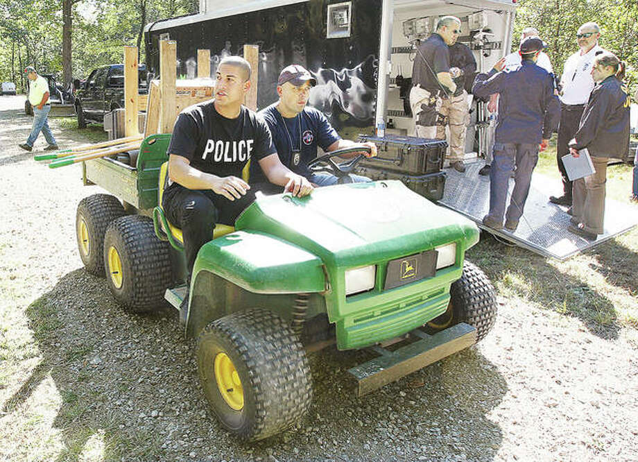 In what was a massive effort by multiple jurisdictions in September 2010, Alton Police officers Marcos Pulido, left, now a sergeant, and Seth Stinnett, right, now a lieutenant, head off on an off-road vehicle to search the Jerseyville property of Roger Carroll, who was suspected in the murder of East Alton woman Bonnie Woodward. According to testimony heard Monday from retired Alton Police Department Capt. Scott Golike, now a special investigator for the Madison County State's Attorney's Office, Roger Carroll's son, Nathan, testified to a grand jury that his father enlisted him in helping burn Woodward's body over the course of eight to 10 days on a brush pile. Photo:     John Badman | The Telegraph