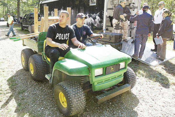 In what was a massive effort by multiple jurisdictions in September 2010, Alton Police officers Marcos Pulido, left, now a sergeant, and Seth Stinnett, right, now a lieutenant, head off on an off-road vehicle to search the Jerseyville property of Roger Carroll, who was suspected in the murder of East Alton woman Bonnie Woodward. According to testimony heard Monday from retired Alton Police Department Assistant Chief Scott Golike, now a special investigator for the Madison County State's Attorney's Office, Roger Carroll's son, Nathan, testified to a grand jury that his father enlisted him in helping burn Woodward's body over the course of eight to 10 days on a brush pile.
