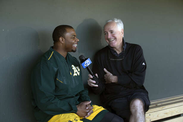 Rajai Davis of the Oakland Athletics talks with Mike Shumann of KGO 7, in the dugout, during a workout at Fitch Park on February 23, 2017 in Mesa, Arizona. (Photo by Michael Zagaris/Oakland Athletics/Getty Images)
