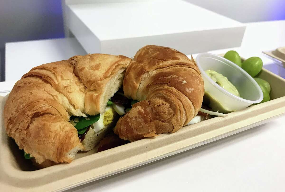 Croissant breakfast sandwich filled with bacon, hard boiled egg and salad with avocado mayonnaise