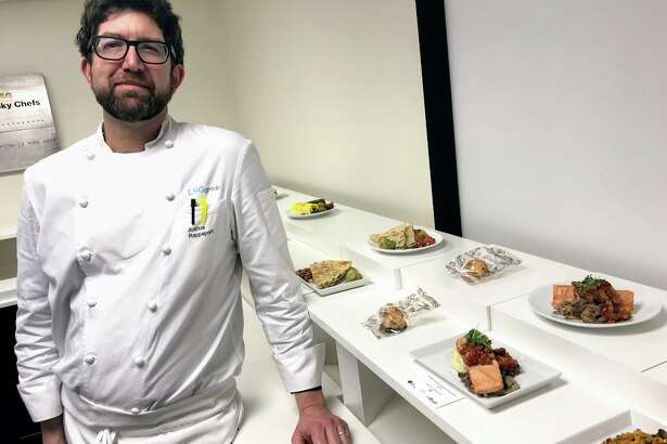 Chef Joshua Rappaport alongside his culinary creations for Alaska Airlines first and economy class passengers