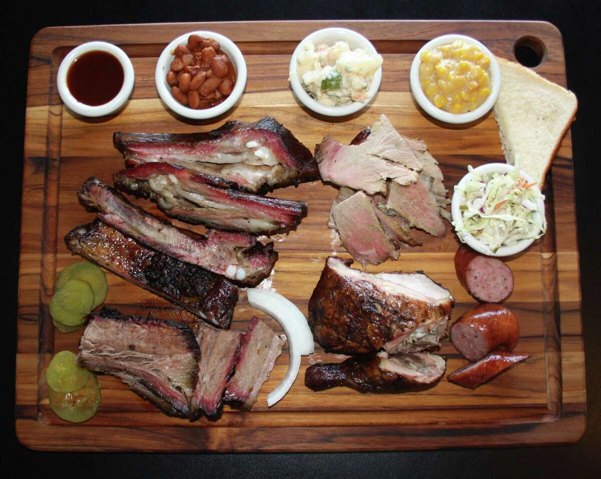 The board from the Old Smokehouse consists of (clockwise from bottom left) brisket, pork spare ribs, lamb ribs, baked beans, potato salad, pork shoulder, creamed corn, cole slaw, sausage and chicken.