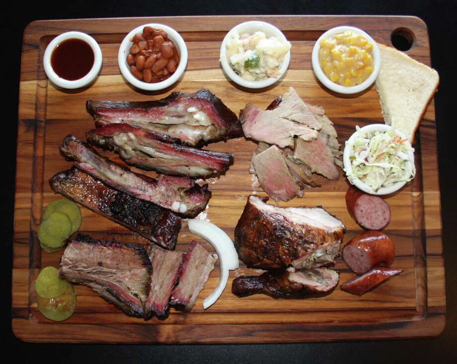 The board from the Old Smokehouse consists of (clockwise from bottom left) brisket, pork spare ribs, lamb ribs, baked beans, potato salad, pork shoulder, creamed corn, cole slaw, sausage and chicken. Photo: Chuck Blount /San Antonio Express-News