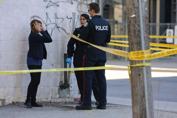 A woman covers her face as  Police have Yonge Street blocked off at Parkview Avenue where on of the victims lies on the East side of the street as the Police investigate a van that ran down pedestrians along Yonge Street between Sheppard and Finch streets in Toronto  at the  Air Canada Centre in Toronto. April 23, 2018.        (Steve Russell/Toronto Star via Getty Images)