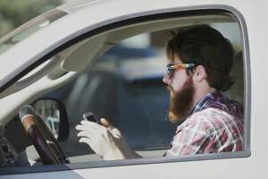 A man uses his cell phone as he drives through traffic in Dallas in 2013.