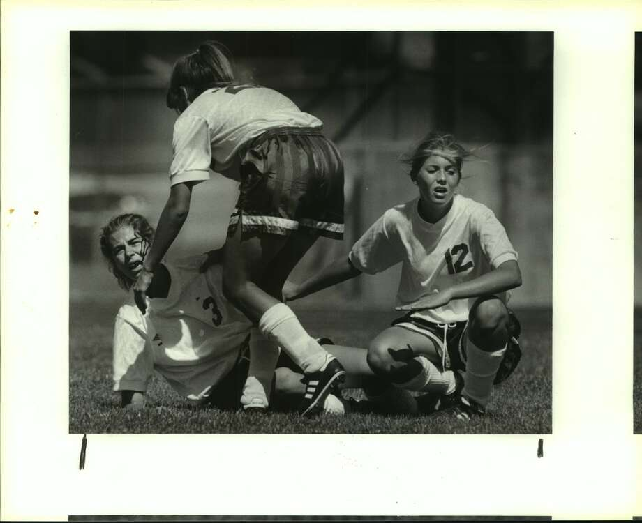 Madison's Holly Barrow (22) and Lisa Malone (12) come to the aid of a bleeding Amy Marlar after Marlar collided with the Plano goalkeeper during the UIL state semifinals in 1993 in Pflugerville. (Express-News file photo)
