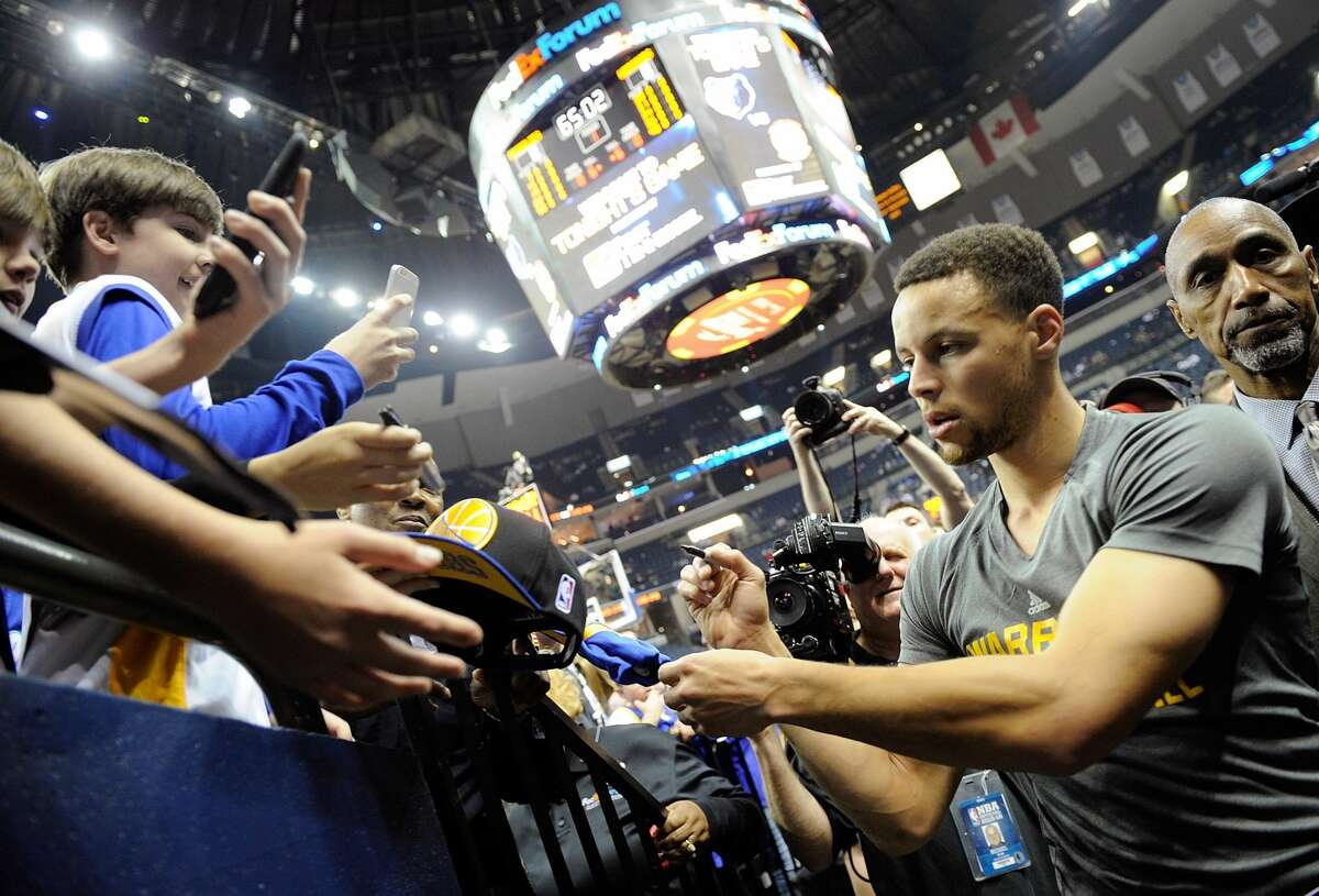 Stephen Curry of the Golden State Warriors signs autographs while accompanied by Ralph Walker, right.