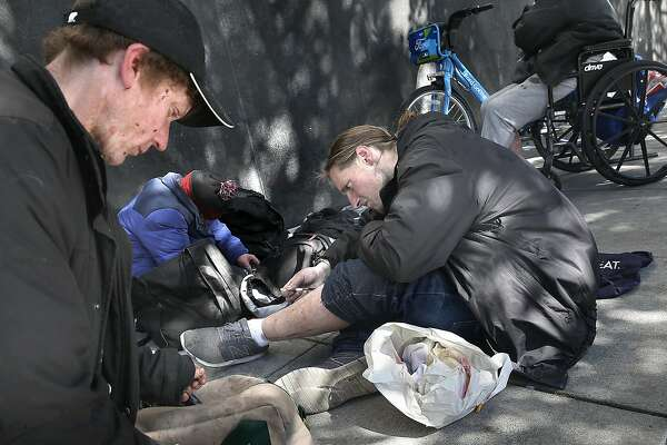 John Cobaugh (far left) shoots heroine with his companions on Mission near 8th streets on Friday, April 20, 2018, in San Francisco, Calif.