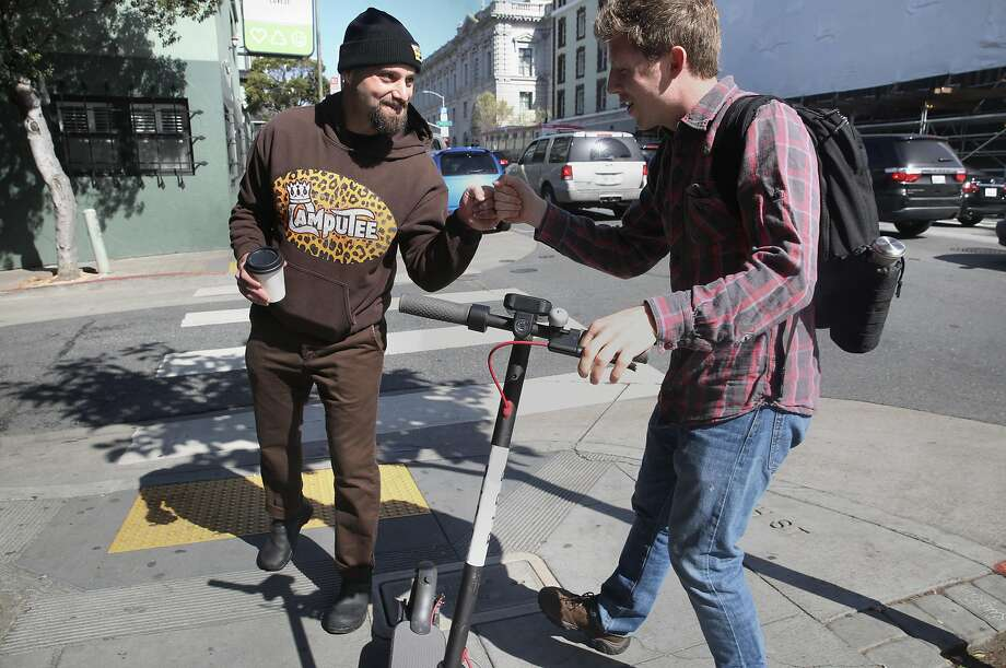 Adam Mesnick (left), who runs two sandwich shops in the sometimes challenging South of Market neighborhood, talks with Drew Lazzeri, who is riding a scooter on Seventh Street. Photo: Liz Hafalia / The Chronicle