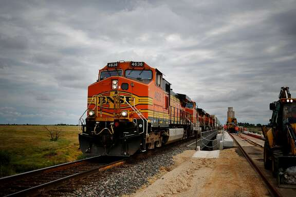 A westbound intermodal train passes by maintenance-of-way workers who are using a track laying machine to construct a second main line on the Burlington Northern Santa Fe (BNSF) Railway Co. Southern Transcontinental line in Alva, Oklahoma,on Aug. 19, 2015. Luke Sharrett/Bloomberg