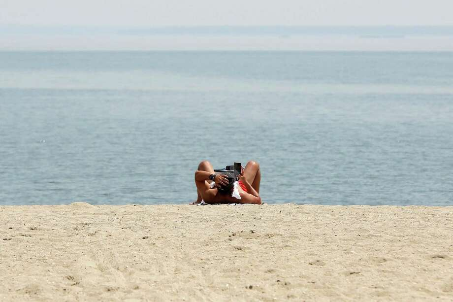 File Photo A Man Scrolls Through His Phone While Lounging On The Sand At Cove