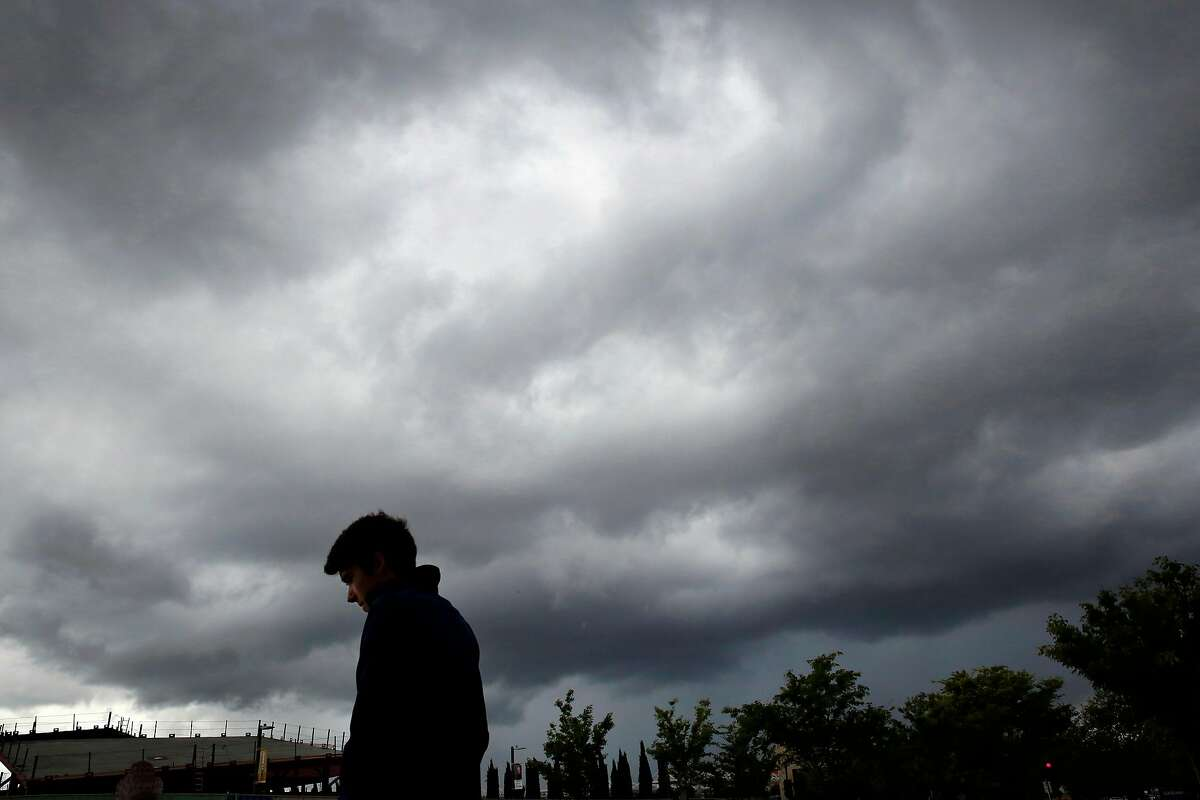 """Daniel Swain checks out a rare thunderstorm as it rolls across the sky during a conference Swain spoke at called """"Water Scarcity in the West: Past, Present, Future"""" at UC Davis April 7, 2015 in Davis, Calif. Swain is a PhD candidate in the Department of Environmental Earth System Science at Stanford University and is also the author of the widely known The California Weather Blog."""