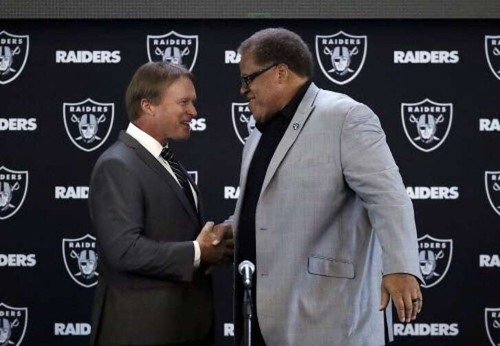 Oakland Raiders head coach Jon Gruden, left, shakes hands with general manager Reggie McKenzie during an NFL football press conference Tuesday, Jan. 9, 2018, in Alameda, Calif. (AP Photo/Marcio Jose Sanchez)