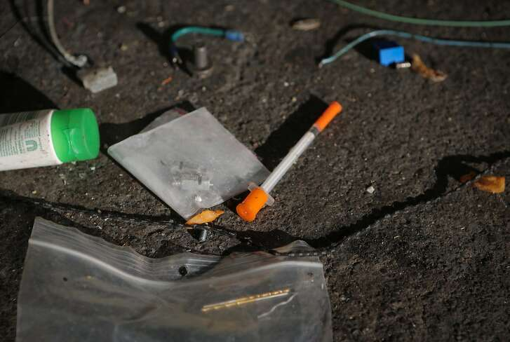 """A hypodermic needle is seen on the sidewalk at a homeless encampment during a San Francisco Public Works Department cleaning at 8th and Brannan Streets in San Francisco, California, on Wednesday, July 1, 2015. The Department's """"alley crew"""" visits homeless encampments on a daily basis to disinfect the ground and haul away refuse."""