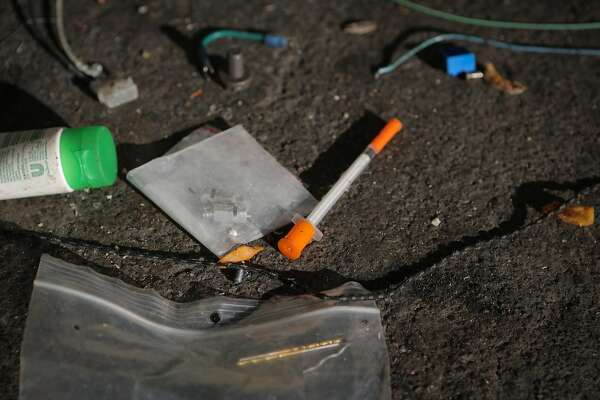 "A hypodermic needle is seen on the sidewalk at a homeless encampment during a San Francisco Public Works Department cleaning at 8th and Brannan Streets in San Francisco, California, on Wednesday, July 1, 2015. The Department's ""alley crew"" visits homeless encampments on a daily basis to disinfect the ground and haul away refuse."