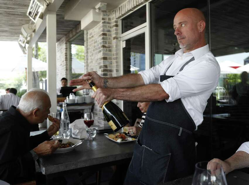 Scott McCune opens a bottle of champagne for a table at a'Bouzy in River Oaks.