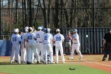 Darien's Sean O'Malley is greeted at home by his teammates after hitting a three-run home run in the sixth inning during an FCIAC baseball game between Darien and Stamford Monday afternoon at Darien High School in Darien, Conn. Darien defeated Stamford 6-2.