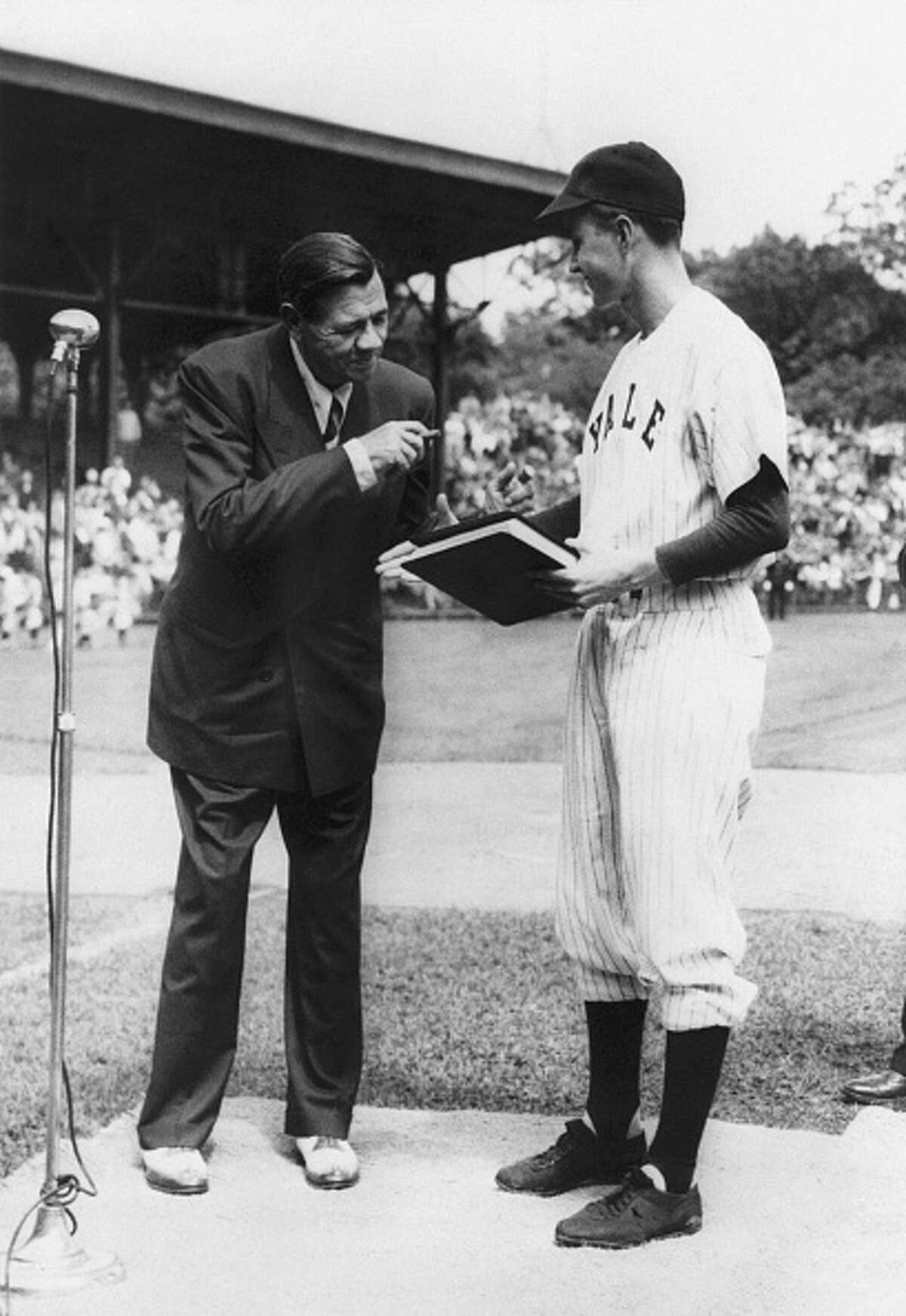 """(Original Caption) 1948-New Haven, CT- George Bush (R) welcomes Babe Ruth (L) at a pre-game ceremony in 1948 at the Yale University field. Bush, captain of the 1948 varsity baseball team, presented a special citation to the """"Babe"""" and in return the legendary home-run king presented a manuscript of The Babe Ruth Story, his biography, for the Yale archives."""
