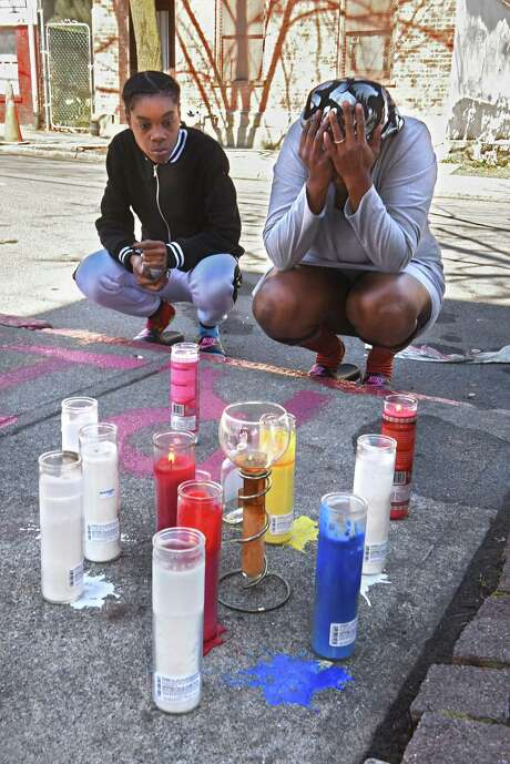 Keessence Coles, left, and Patricia McMillian, both of Albany, take a moment of silence after bringing flowers and lighting a candle they also brought for their friend's memorial on Clinton St. near Second Ave. on Monday, April 23, 2018 in Albany, N.Y. Their friend, Damien Sanders, was 38-years-old and was shot multiple times at this location. (Lori Van Buren/Times Union) Photo: Lori Van Buren / 40043578A