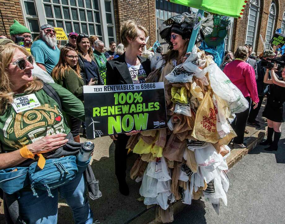 Cynthia Nixon, Democratic challenger for governor, left, speaks with Sloan Brockmann of Lynbrook, L.I. who was dressed in plastic bags for the Walk the Talk on Climate! Day of Action before they marched on the State Capitol building on Monday, April 23, 2018, in Albany, N.Y.  (Skip Dickstein/Times Union) Photo: SKIP DICKSTEIN / 20043570A