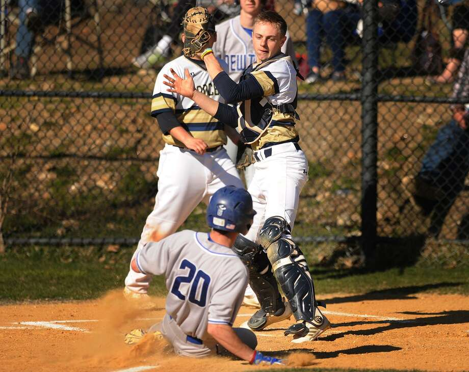 Newtown's Harry Eppers slides in safely to home as Notre Dame of Fairfield catcher Jacob Rainey takes the throw during a six run first inning in their SWC baseball game at Notre Dame High School in Fairfield, Conn. on Monday, April 23, 2018. Photo: Brian A. Pounds / Hearst Connecticut Media / Connecticut Post