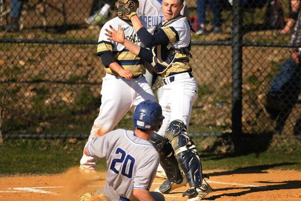 Newtown's Harry Eppers slides in safely to home as Notre Dame of Fairfield catcher Jacob Rainey takes the throw during a six run first inning in their SWC baseball game at Notre Dame High School in Fairfield, Conn. on Monday, April 23, 2018.