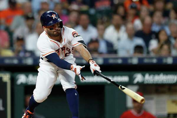 Houston Astros second baseman Jose Altuve (27) singles as Los Angeles Angels Kole Calhoun missed the pop up during the third inning of an MLB game at Minute Maid Park, Monday, April 23, 2018, in Houston.