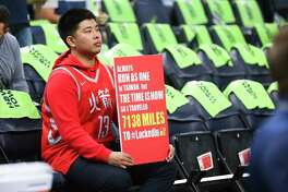 Meng-Han Yang, who traveled from Taiwan to see the Houston Rockets play, holds a sign behind the bench before the Rockets take on the Minnesota Timberwolves in Game 4 of the first round of the NBA Playoffs at Target Center Monday, April 23, 2018 in Minneapolis.