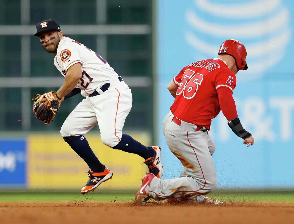 Houston Astros second baseman Jose Altuve (27) tags Los Angeles Angels Kole Calhoun (56) out at second during the fifth inning of an MLB game at Minute Maid Park, Monday, April 23, 2018, in Houston.