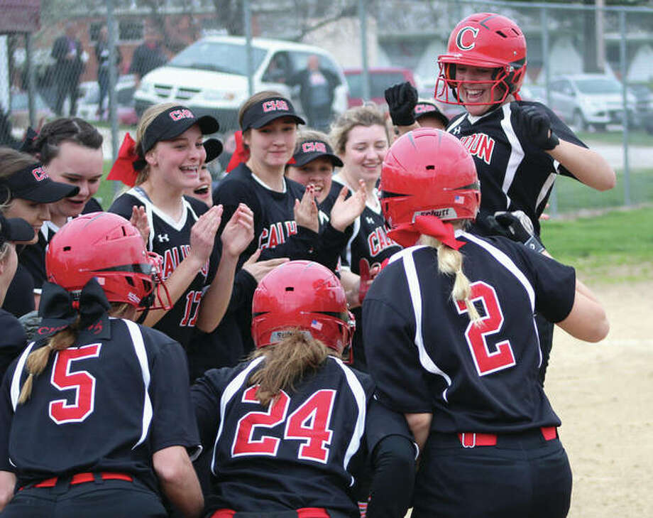 Sydney Baalman (right) is greeted by her Calhoun teammates at home plate after hitting a grand slam in the third inning to give the Warriors a 4-2 lead. The Tigers would answer with a 10-run inning in the fourth on their way to a 14-6 victory Monday in Hardin. Photo:     Greg Shashack / For The Telegraph